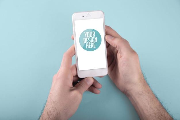 両手明るい青の背景で白いスマートフォンを使用している人