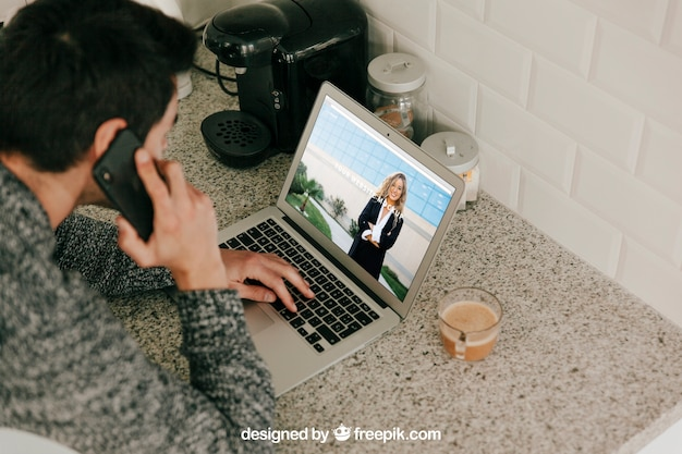 Man using laptop and making phone call