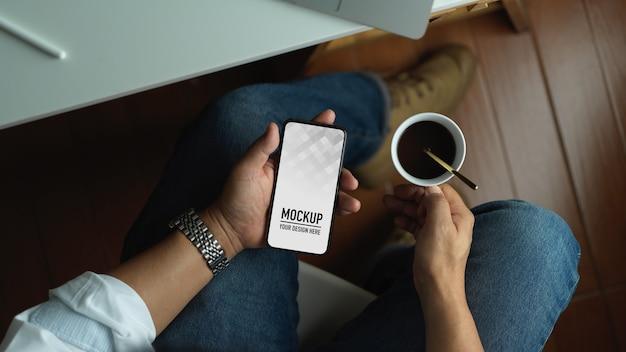 Человек, использующий смартфон с пустым экраном макета и держащий чашку кофе, сидя в офисной комнате
