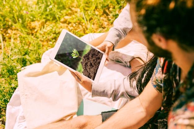 자연에서 태블릿 이랑을 사용하는 사람 무료 PSD 파일