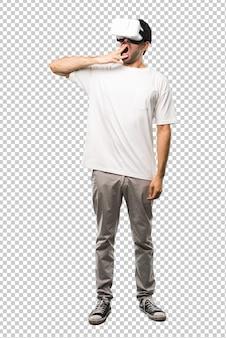 Человек, используя очки vr зевая и прикрывая широко открытый рот рукой