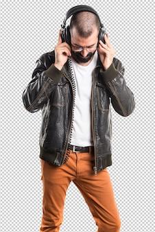 音楽を聴く革ジャケットを着ている男