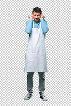 Человек, носящий фартук, закрывающий оба уха руками. разочарованное выражение