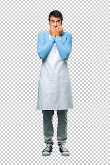 Man wearing an apron covering mouth with both hands for saying something inappropriate.