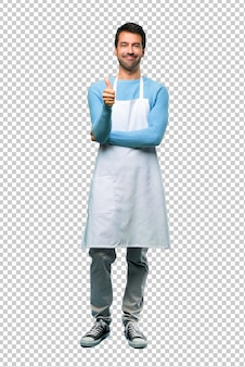 Man wearing an apron giving a thumbs up gesture and smiling because something good has happened