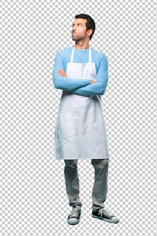 Man wearing an apron having doubts and with confuse face expression while bites lip.