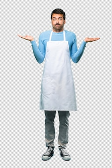Man wearing an apron having doubts and with confuse face expression while raising hands