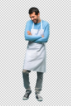 Man wearing an apron keeping the arms crossed while smiling
