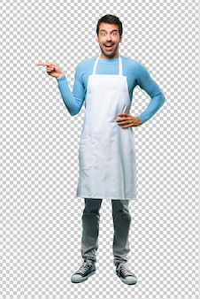 Man wearing an apron pointing finger to the side and presenting