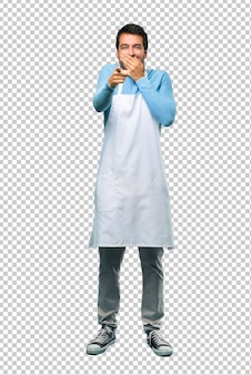 Man wearing an apron pointing with finger at someone and laughing a lot while covering mouth