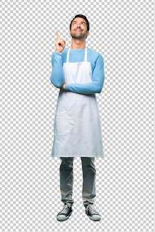 Man wearing an apron pointing with the index finger a great idea and looking up
