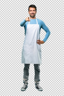 Man wearing an apron points finger at you with a confident expression