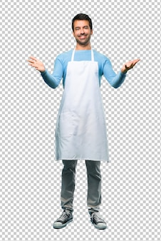 Man wearing an apron presenting and inviting to come with hand. happy that you came