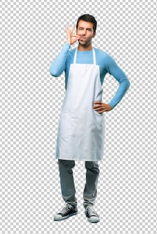 Man wearing an apron showing a sign of closing mouth and silence gesture