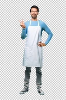 Man wearing an apron smiling and showing victory sign with a cheerful face