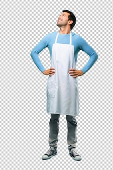 Man wearing an apron stand and looking up