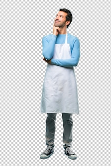 Man wearing an apron standing and thinking an idea while looking up