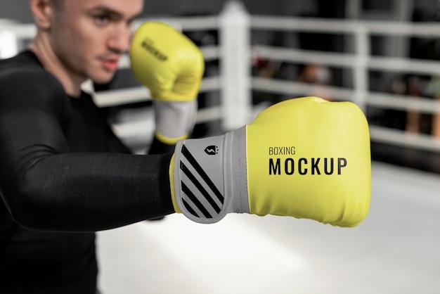 Uomo che indossa guantoni da boxe mock-up per la formazione