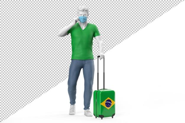フェイスマスクを身に着けている男は、ブラジルの旗でテクスチャリングされたスーツケースを引っ張る