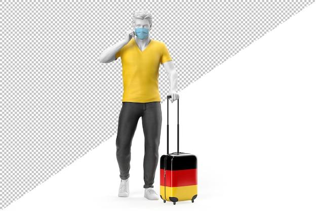 フェイスマスクを身に着けている男は、ドイツの旗でテクスチャリングされたスーツケースを引っ張る