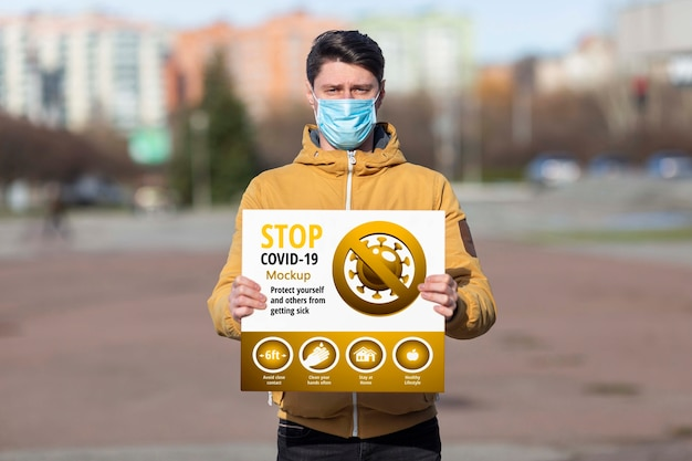 Man wearing a mask holding a coronavirus stop mock-up