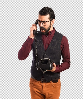 Man wearing waistcoat talking to vintage phone