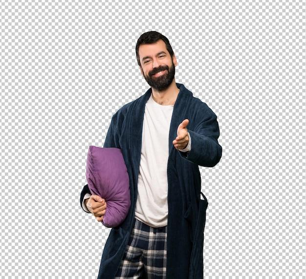 Мужчина с бородой в пижаме пожимает руку за заключение хорошей сделки