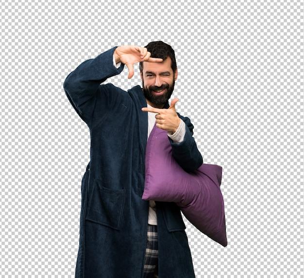 Man with beard in pajamas focusing face. framing symbol
