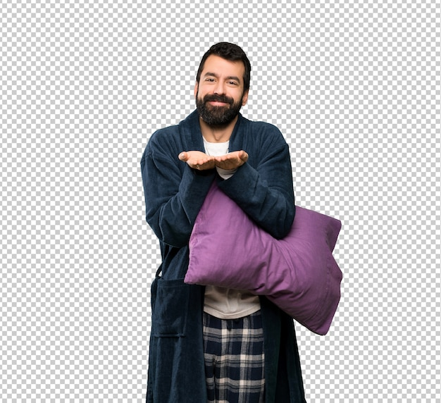 Man with beard in pajamas holding copyspace imaginary on the palm to insert an ad