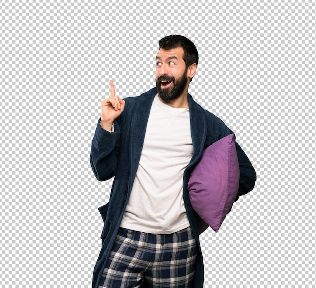 Man with beard in pajamas intending to realizes the solution while lifting a finger up