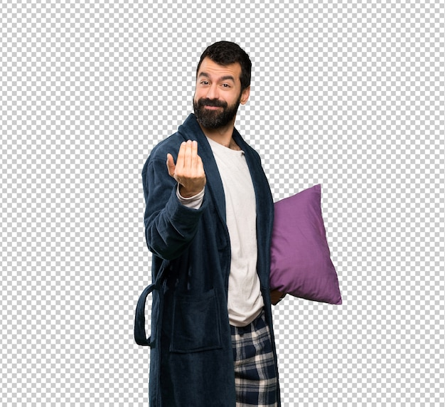 Man with beard in pajamas inviting to come with hand. happy that you came