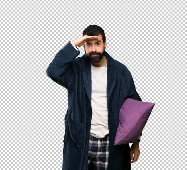 Man with beard in pajamas looking far away with hand to look something