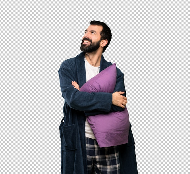 Man with beard in pajamas looking up while smiling