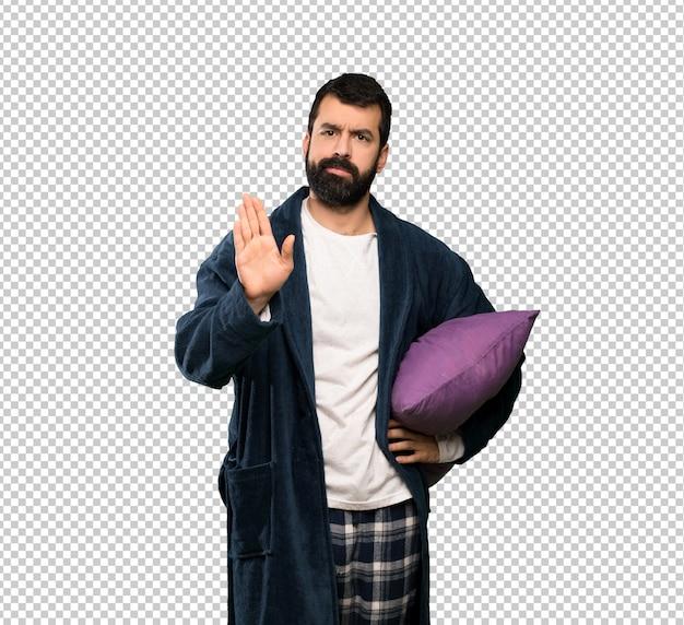 Man with beard in pajamas making stop gesture