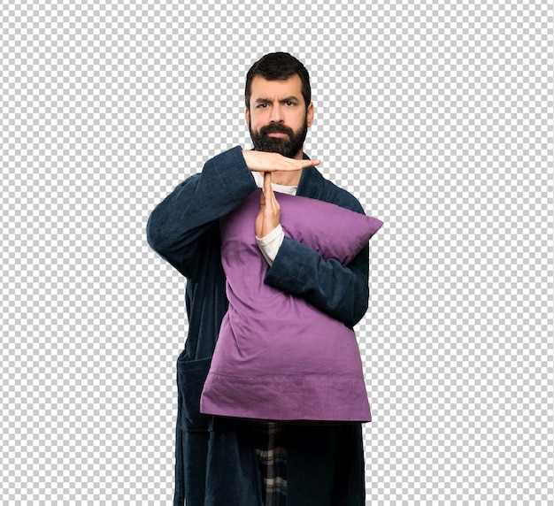 Man with beard in pajamas making time out gesture
