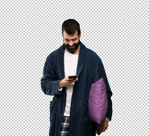 Man with beard in pajamas sending a message with the mobile
