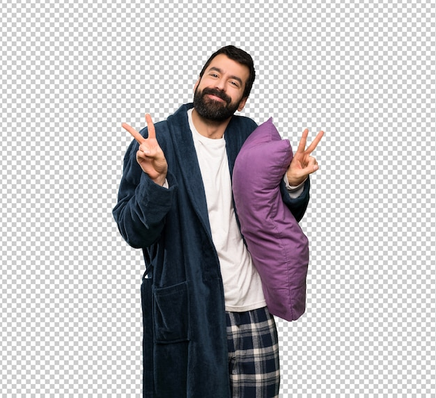 Man with beard in pajamas showing victory sign with both hands