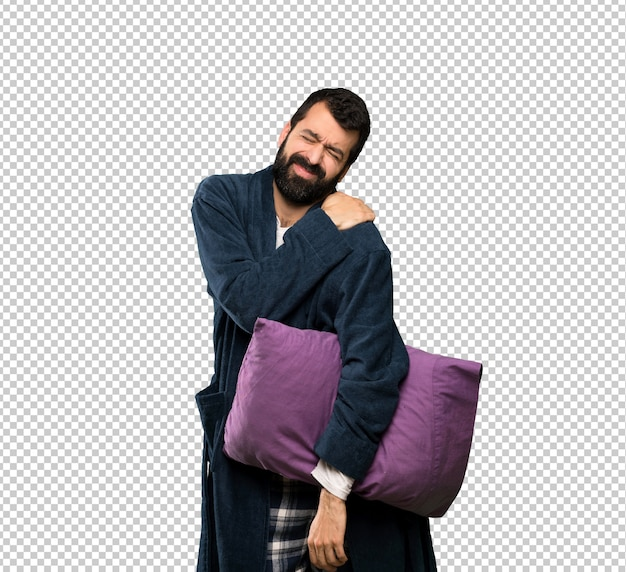 Man with beard in pajamas suffering from pain in shoulder for having made an effort