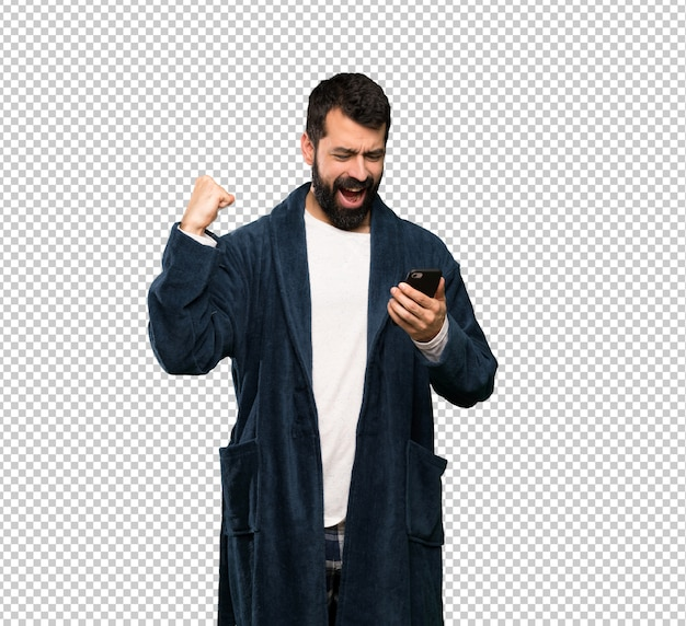 Man with beard in pajamas with phone in victory position
