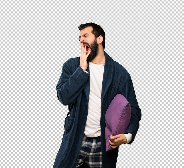 Man with beard in pajamas yawning and covering wide open mouth with hand