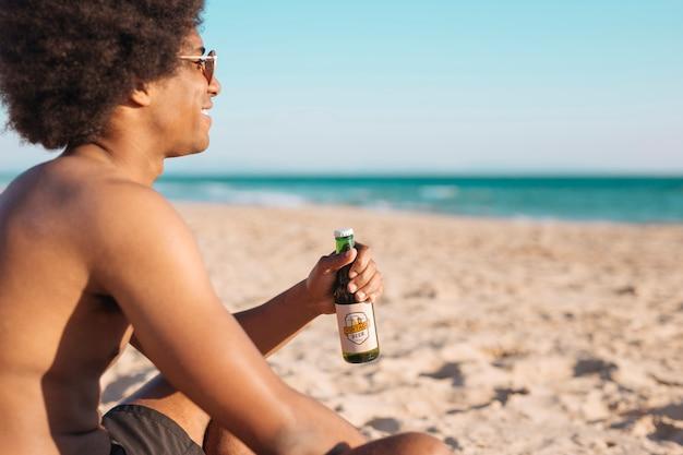 Uomo con il modello di bottiglia di birra in spiaggia