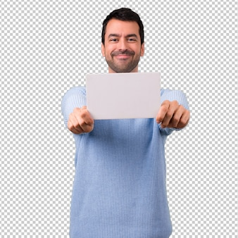 Man with blue sweater holding an empty white placard for insert a concept