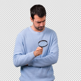 Man with blue sweater holding a magnifying glass