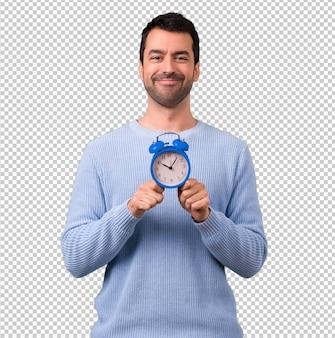 빈티지 알람 시계를 들고 파란 스웨터를 가진 남자