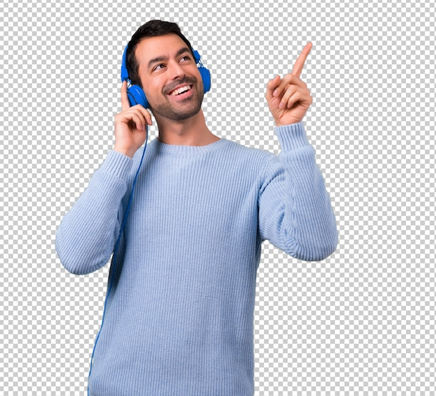 Man with blue sweater listening to music with headphones