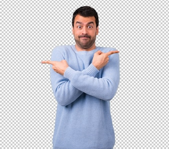 Man with blue sweater pointing to the laterals having doubts. Undecided person