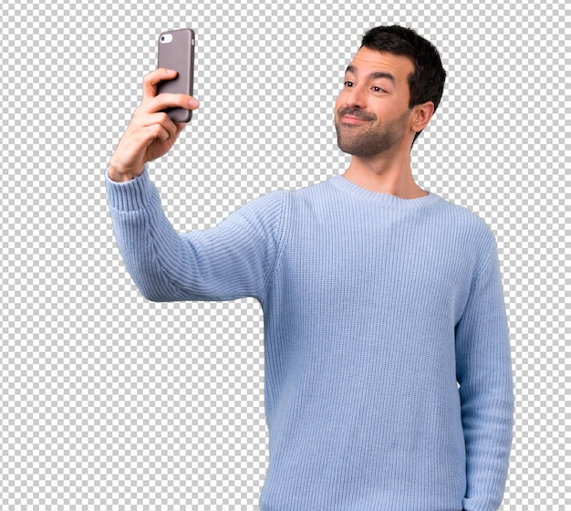 Man with blue sweater using mobile phone