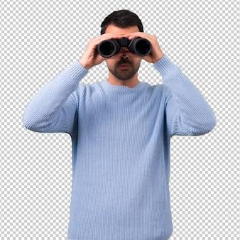 Man with blue sweater with black binoculars