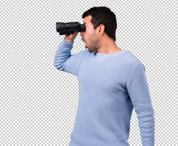 검은 쌍안경으로 파란색 스웨터를 가진 남자