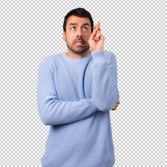 Man with blue sweater with fingers crossing and wishing the best. making a wish.